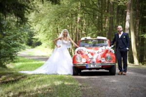 Brautpaar mit geschmückten VW Käfer im Wald