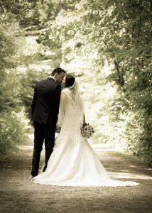 Hochzeitsfoto im Wald, Ehepaar küsst sich