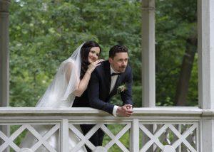 Ehepaar steh in einem Pavillon, sie lehnt an ihm und schaut verträumt