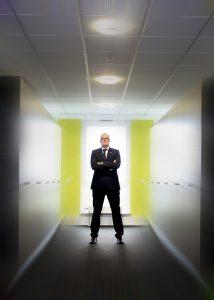 Geschäftsmann steht im Flur, dieser wirkt wie ein Tunnel