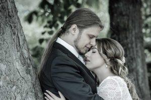 Hochzeitspaar hält sich mit geschlossenen Augen im Arm, er lehnt an einem Baum