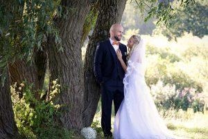 Hochzeitspaar lächelt sich an, er leht an einem großen Baum sie lehnt an ihm
