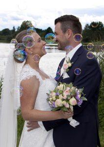 Hochzeitspaar schaut sich verträumt an, Seifenblasen um sie herum, See und Grün im Hintergrund