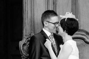 Hochzeitspaar lehnt an einer alten großen Holztür, schwarzweiß-fotografie, lächelt sich gegenseitig an, die Nasenspitzen berühren sich