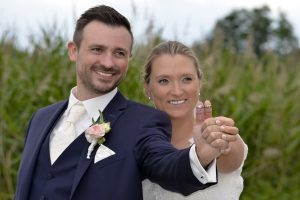 Hochzeitspaar halten beide den Daumen hoch, an beiden Daumen ist der jeweilige Ehering und darunter ein lächeldes Gesicht auf dem Daumengemalt