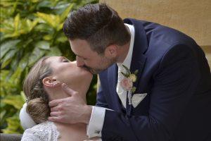 Hochzeitspaar küsst sich während sie sitzt und er steht und sich nach unten beugt