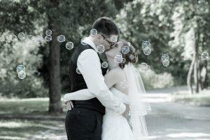 Hochzeitspaar küsst sich, umgeben von Seifenblasen