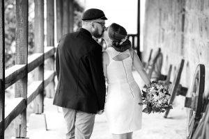 Hochzeitspaar küsst sich ist von hinten zu sehen läuft eine Art Scheune entlang mit Wagenrädern an der Wand