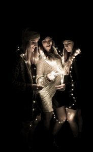 Drei junge Frauen im Dunkeln mit Lichterkette