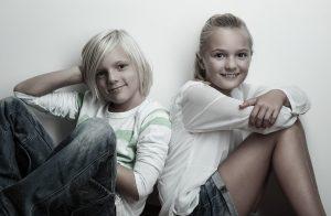 Geschwister sitzen Rücken an rücken und lächeln leger in die Kamera