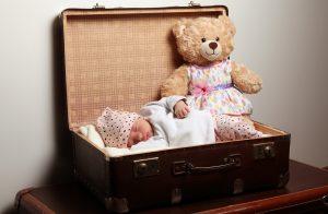 frisch geborenes Baby liegt mit einem teddy in einem ausgepolsterten Koffer, schläft