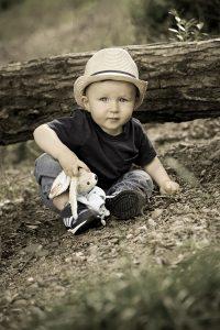 Kleinkind mit Teddy und Hut sitzt auf Waldboden