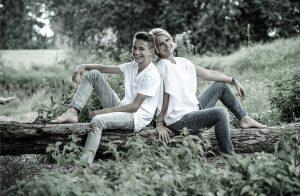 Portrait von mutter und Sohn im Wald, rücken an Rücen, lächelnd auf einem baumstumpf sitzend