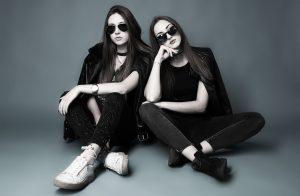Zwei junge Frauen, fast komplett schwarz gekleidet sitzen mit dunklen Sonnenbrillen leger auf dem Studioboden