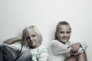 Blondes Geschwisterpaar: Junge und Maedchen sitzten Rücken an Rücken, blicken direkt in die Kamera, lächeln