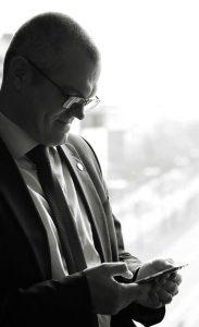 Businessfototgrafie eines Mannes, vor sich hin schmunzelnd, im anzug da stehend und auf sein Handy schauend, schwarzweiß-fotografie
