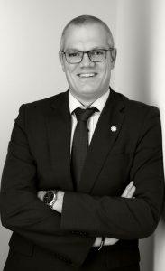Businessfototgrafie eiens Mannes im anzug, lächelnd, an eie Wand gelehnt, schwarz-weiß-fotografie