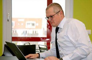 Businessfototgrafie eines Mannes im Anzug, auf den Laptop schauend
