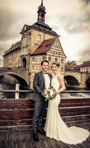 Hochzeitsaar steht in Bamberg auf einer Brücke, das alte Rathaus im Hintergrund
