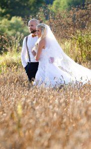 Hochzeitstag: Ehepaar steht in einem Kornfeld, mit Blick in die Weite schweifend