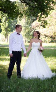 Hochzeitspaar schaut sich verliebt an, steht auf einer Wiese