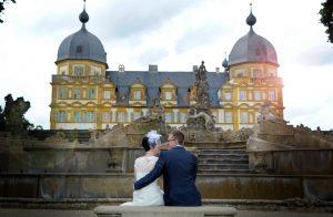 Ehepaar sitzt vor Schloss Seehof