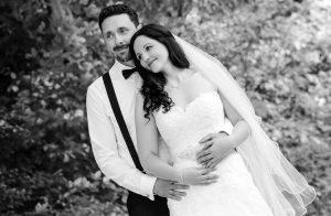 Verträumt schauendes Hochzeitspaar, er steht hinter ihr und hält sie im Arm, Hintergrund ist verschwommen und schemenhaft ist ein großer Baum zu sehen