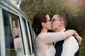 Hochzeitspaar küsst sich, lehnt dabei an altem VW-Bus