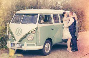 Hochzeitspaar steh an einem alten VW-Bus gelehnt, sich anblickend und sich umarmend