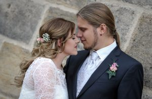 Hochzeitspaar steht Stirn an Stirn mit geschlossenen Augen, HIntergrund ist eien Steinmauer