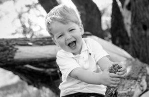 lachendes blondes Kind im Wald, auf einem Ast sitzend mit weißem Poloshirt