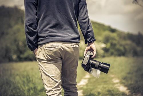 Grüner Waldweg auf dem der Chef des Fotostudios Peter Schiller von hinten zu sehen ist, in der Hand hält er eine Kamera, die andere Hand ist leger in die Tasche gesteckt