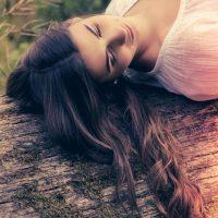 Junge Frau liegt auf einem Baumstamm, schaut verträumt in die Gegend