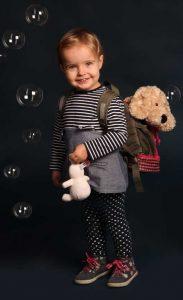 Portraitfoto eines Kleinindes in Seifenblasen eingehüllt, mit Rucksack auf dem Rücken in welchem eine teddy steckt