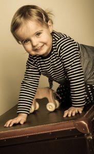 Portraitfoto eines Kleinkindes welches auf einem Koffer krabbelt und lächelt