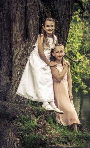 Portraitfoto von zwei jungen Mädchen die in schicken weißen Kleidern im Wlad stehen und lächen