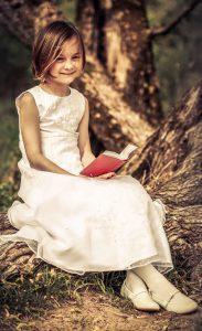 Portraitfoto eines jungen Mädchen in weißem Kleid, mit Gebetbuch in der Hand, in die Kamera lächelnd