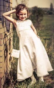 Portraitfoto eines jungen Mädchens in Kommunionskleid, an eine Wand gelehnt