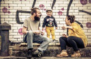Familie mit Kleinkind sitzt auf dem Randstein, mit buntem Grafitti-besprühte Mauer ist im hintergrund