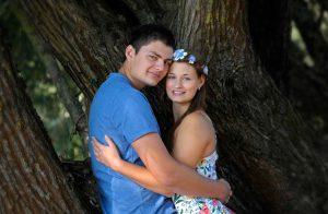 Pärchen umarmt sich und lehnt an einem Baumstamm