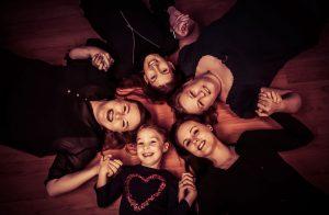 Gruppe von Freundinnen liegt auf dem Boden im Kreis, Köpfe aneinander und halten sich an den Händen, Foot wurde von oben gemacht