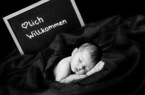 Babyshooting, Baby schläft, liegt eingehüllt in Decken, hinter ihm liegt eine Tafel die mit Herzlich willkommen beschrieben ist