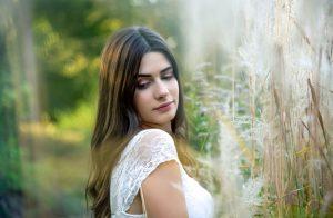 Portraitfoto einer jungen, hübschen Frau die verträumt im Wald steht und nach unten schaut, Hintergrund ist verschwommen