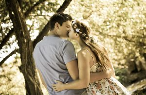 Portraitfoto eines sich küssenden Paares welches im Wald steht und von hinten fotografiert wurde