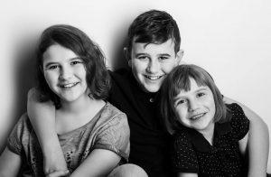 Portraitfoto von 3 Kindern die sich im Arm halten, Schwarzweißfotografie