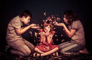 Portraitfoto von 3 Kindern die alle ganz viele Papierherzen in den Händen halten und pusten um sie übereinander zu verteilen