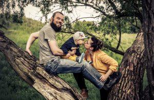 Portrait von Familie mit einem kleinkind im Wlad auf einem Baum kletternd, die Mutter ist dabei das Kind zu küssen, Vater schuat in die Kamera