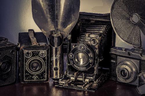 alte Kameras aus den circa 20-er Jharen auf einem Tisch stehen